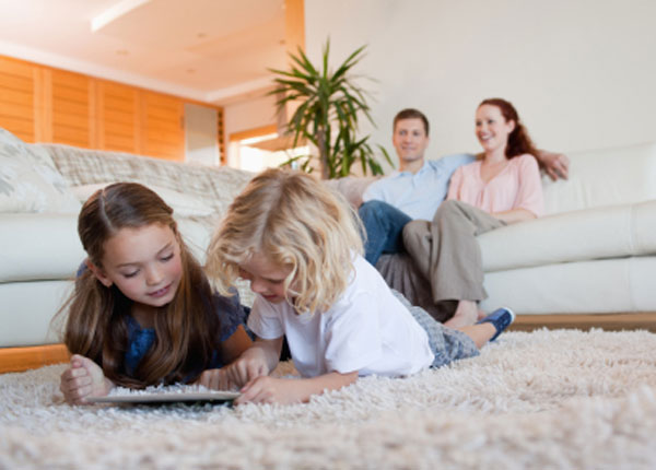 Children using tablet on the carpet
